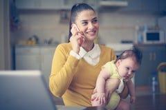 Mime a detener a su pequeño bebé en brazos y a hablar el teléfono fotografía de archivo