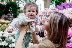 Mime a detener a un bebé masculino cerca de las flores de un flor Fotografía de archivo libre de regalías