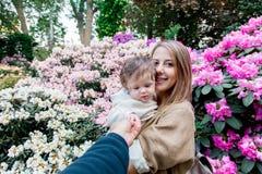 Mime a detener a un bebé masculino cerca de las flores de un flor Fotos de archivo libres de regalías