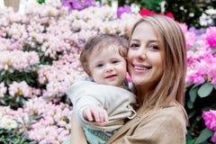 Mime a detener a un bebé masculino cerca de las flores de un flor Fotografía de archivo