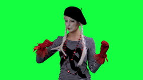 The mime drinks tea from a cup invisible. The girl mime against a green background