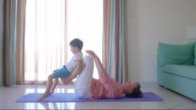 Mime a ejercicio con su hijo en la estera de la aptitud en la sala de estar almacen de metraje de vídeo