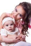 Mime en un vestido rosado con una hija 6 meses en el vestido blanco Imágenes de archivo libres de regalías