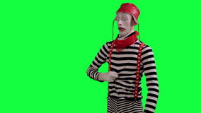 The mime feels stuffy and hot. The boy mime against a green background stock video