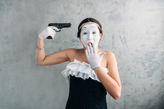 Mime female artist performing with gun stock images