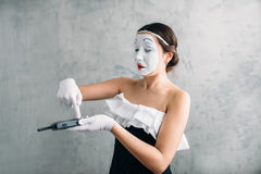 Mime female artist performing with mobile phone stock images