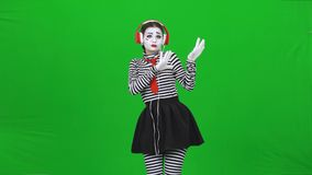 Mime female listening to the music through headphones. Chroma key. Mime female with professional make-up, dressed in striped turtleneck and leggings is acting stock video