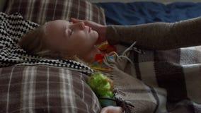 Mime a frotar ligeramente a su hija durmiente en la cama almacen de video