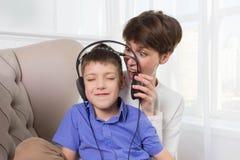 Mime a griterío a su hijo mientras que él el ` t de la música que escucha y del doesn escucha Fotografía de archivo libre de regalías