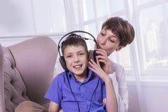Mime a griterío a su hijo mientras que él el ` t de la música que escucha y del doesn escucha Imagenes de archivo