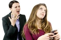 Mime a grito y a griterío en la hija que charla con el teléfono Imagen de archivo