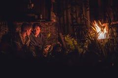 Mime a hablar con su hijo maduro del adolescente alrededor de la hoguera en la noche en campo Imagenes de archivo