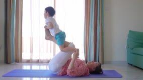 Mime a hacer entrenamiento de la yoga en casa con el hijo joven lindo almacen de metraje de vídeo