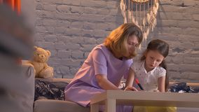 Mime a hacer la preparación con su pequeña hija, niño de ayuda del padre con el estudio, concepto de familia dentro metrajes