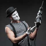 Mime with hammer drill Stock Photos