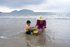 Mime a jugar con su hijo en la arena en la orilla de mar fotografía de archivo