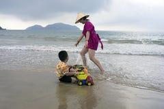 Mime a jugar con su hijo en la arena en la orilla de mar foto de archivo libre de regalías