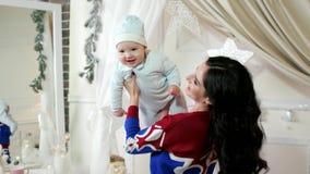 Mime a jugar con su pequeño hijo, niño, bebé en los brazos de su madre, la diversión de la familia que juega durante el invierno almacen de metraje de vídeo