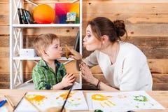 Mime a la cara conmovedora del hijo con las manos pintadas en pinturas Imágenes de archivo libres de regalías
