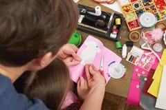 Mime a la hija de enseñanza para coser la ropa de la muñeca, visión superior, cosiendo los accesorios visión superior, lugar de t Imagen de archivo
