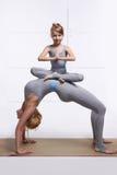 Mime a la hija que hace el ejercicio de la yoga, aptitud, gimnasio que lleva los mismos chándales cómodos, deportes de la familia Fotos de archivo