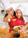 Mime a la hornada con la pequeña hija en delantal y cocine los molletes del molde del relleno del sombrero con pasta del chocolat fotografía de archivo