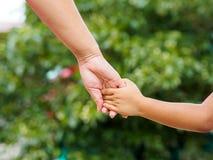 Mime a la mano del ` s que lleva a cabo una mano del ` s de la niña en fondo del bokeh Fotos de archivo