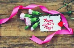 Mime a la postal del día del ` s, a los claveles rosados y a la nota foto de archivo