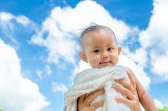 Mime lanzan para arriba a la hija del bebé con la toalla en fondo del cielo azul Fotografía de archivo libre de regalías