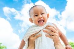 Mime lanzan para arriba a la hija del bebé con la toalla en fondo del cielo azul Imagenes de archivo