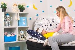 Mime a las medidas la temperatura con su mano a su niño Un niño con la fiebre que pone en cama fotos de archivo