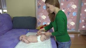 Mime a las pequeñas piernas del masaje y de la hija del bebé del ejercicio en cama 4K metrajes