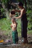 Mime a lavar a su niño vertiéndolo fuera de un cubo con agua en una calle del pueblo imagen de archivo