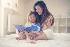 Mime a leer a su hija la historia después de despertar Wi de la madre fotos de archivo