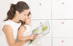 Mime a leer un libro a su pequeña hija en casa Fotografía de archivo libre de regalías