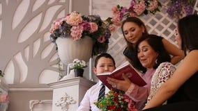 Mime a leer un libro a sus niños en el jardín de flores metrajes