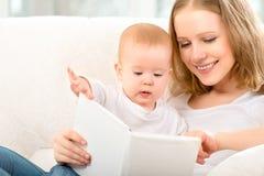 Mime a leer un libro un pequeño bebé en el sofá Fotografía de archivo libre de regalías