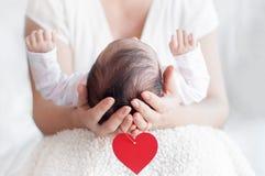 Mime a llevar a cabo la cabeza de su bebé recién nacido en manos Familia feliz c imagen de archivo