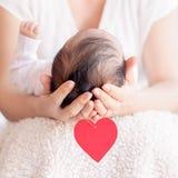 Mime a llevar a cabo la cabeza de su bebé recién nacido en manos Familia feliz c imágenes de archivo libres de regalías