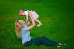 Mime a los controles del las manos su pequeño bebé en una hierba Fotografía de archivo