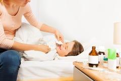 Mime a los descensos nasales de caída a su hijo enfermo del niño Imágenes de archivo libres de regalías
