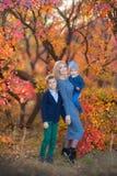 Mime a los hermanos lindos hermosos del womanwithTwo de la señora que se sientan en la calabaza en bosque del otoño solamente Fotos de archivo