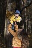 Mime a los juegos con el niño de risa, lanzándolo para arriba para arriba contra Foto de archivo libre de regalías