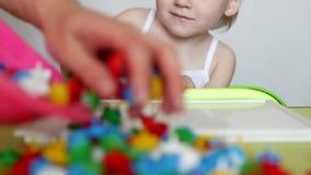 Mime a los juegos con el niño en las habilidades de motor del juego que se convierten, recoja un mozayku multicolor del ` s de lo almacen de metraje de vídeo