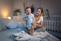 Mime a los pañales sucios cambiantes a su bebé en cama en la noche Imagenes de archivo