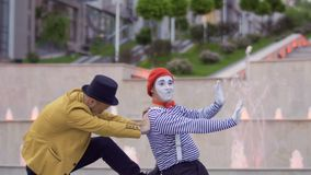Mime and magician compete who is better. Two street actors have fun together and show each other their professional skills. People are standing on the urban stock video footage