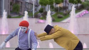 Illusionist and funny mime compete who is better. Mime and magician compete who is better. Two street actors have fun together and show each other their stock video