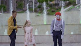 Mime and magician fighting for the girl`s attention showing her their skills. Illusionist and mime are showing performance at the urban street near fountains stock video footage