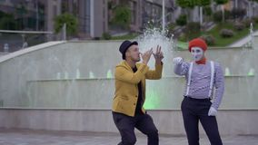 Mime and magician have fun near illuminated fountains. Ilusionist and mime have fun standing near the illuminated fountains at the urban street. Two street stock video footage