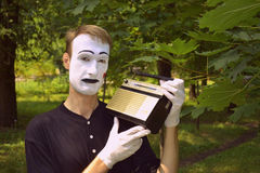 Mime and old radio receiver. The guy the mime listens old to radio the receiver Stock Photography